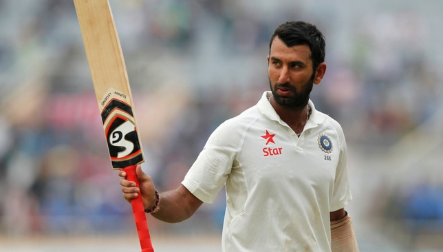 Pujara lifts his bat to the crowd after his knock [Sportzpics]