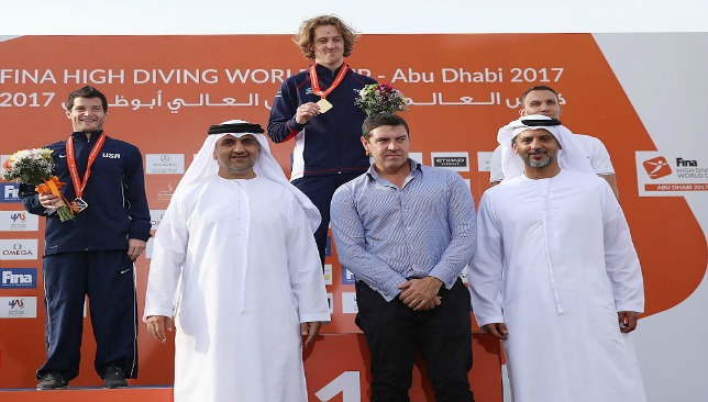 Britain's Gary Hunt (c) celebrates gold in Abu Dhabi
