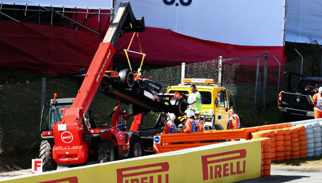 Fernando Alonso's car being removed from the circuit after it broke down.