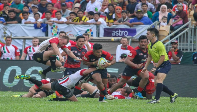 Kris Greene (l) and Luke Stevenson attempt to stop Malaysia's Badrul Bin Muktee