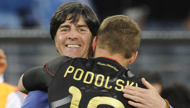 Joachim Loew hugs striker Lukas Podolski after their win over Argentina.