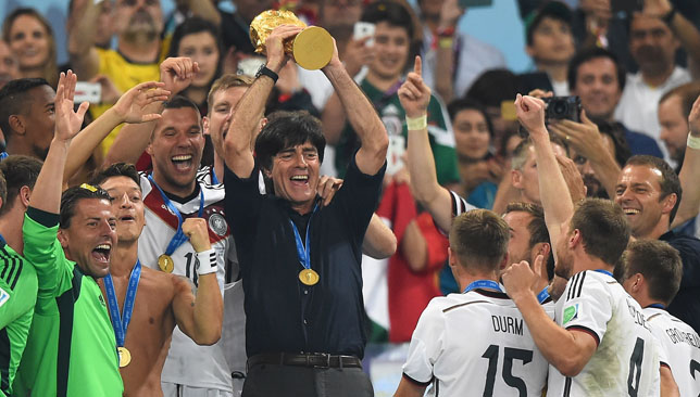 Loew lifts the World Cup trophy.