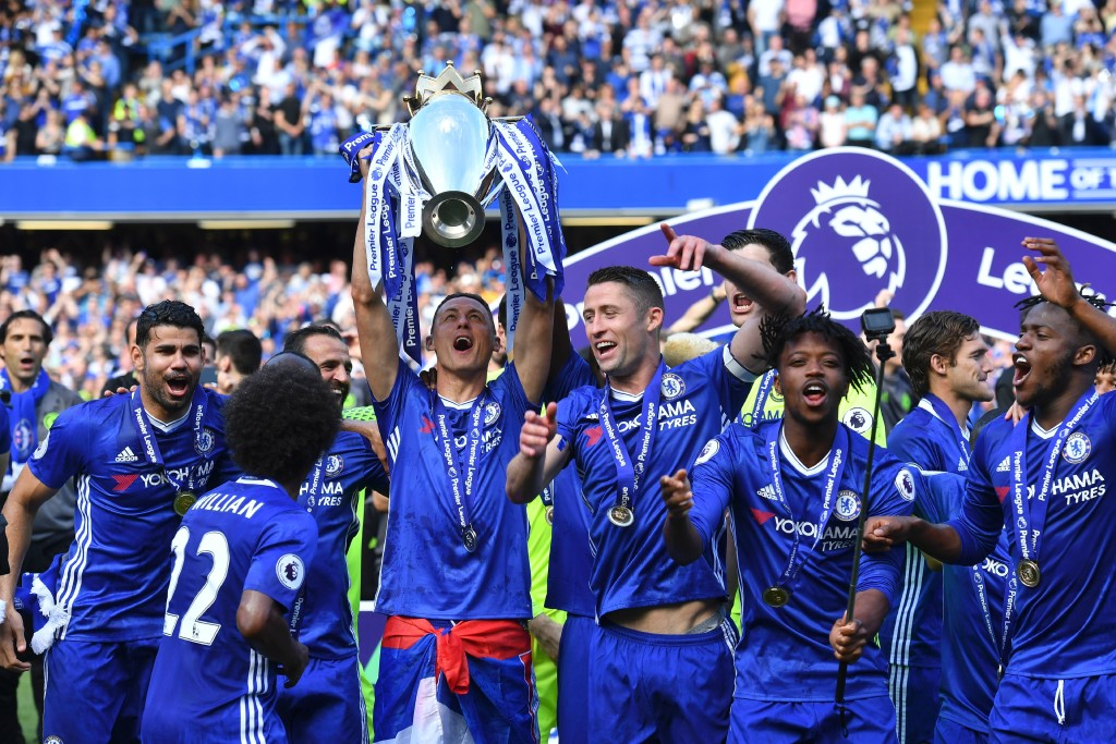 Chelsea's Serbian midfielder Nemanja Matic holds up the English Premier League trophy, as players celebrate their league title win at the end of the Premier League football match between Chelsea and Sunderland at Stamford Bridge in London on May 21, 2017. Chelsea's extended victory parade reached a climax with the trophy presentation on May 21, 2017 after being crowned Premier League champions with two games to go. / AFP PHOTO / Ben STANSALL / RESTRICTED TO EDITORIAL USE. No use with unauthorized audio, video, data, fixture lists, club/league logos or 'live' services. Online in-match use limited to 75 images, no video emulation. No use in betting, games or single club/league/player publications. / (Photo credit should read BEN STANSALL/AFP/Getty Images)