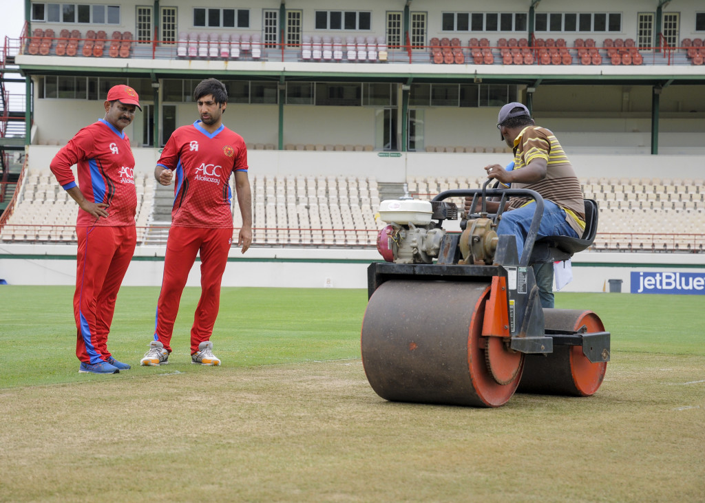 Lalchand Sitaram Rajput (L) and Mohamad Asghar Stanikzai (2L) of Afghanistan chat about the pitch as ground staff use a roller during a training session at Darren Sammy National Cricket Stadium on June 08, 2017 in St. Lucia ahead of the West Indies vs Afghanistan ODI game scheduled on June 09, 2017. / AFP PHOTO / Randy Brooks (Photo credit should read RANDY BROOKS/AFP/Getty Images)