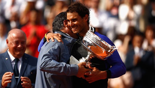 Rafael Nadal receives the French Open trophy from his uncle and coach Toni Nadal.