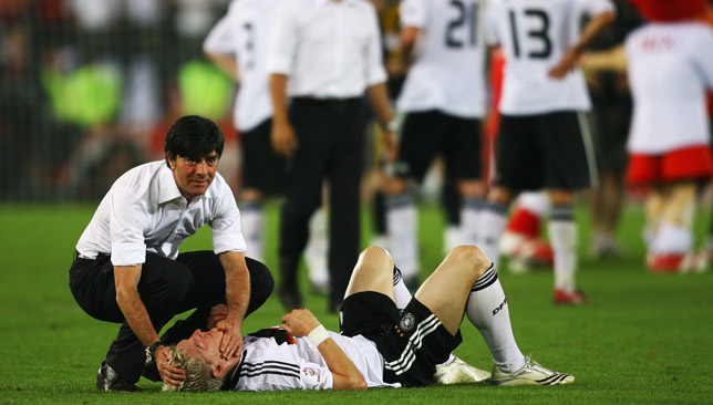 Joachim Loew comforts Bastian Schweinsteiger after their defeat to Spain.