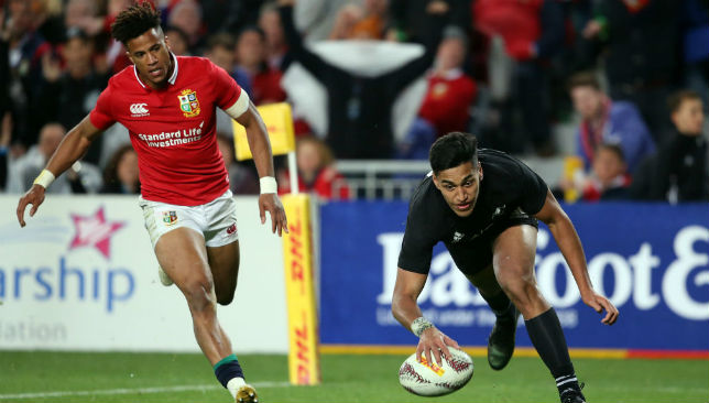 Rieko Ioane (R) scores a try with Anthony Watson of the Lions chasing (L).
