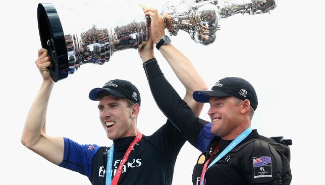 Peter Burling (l) and Glenn Ashby raise the America's Cup aloft.