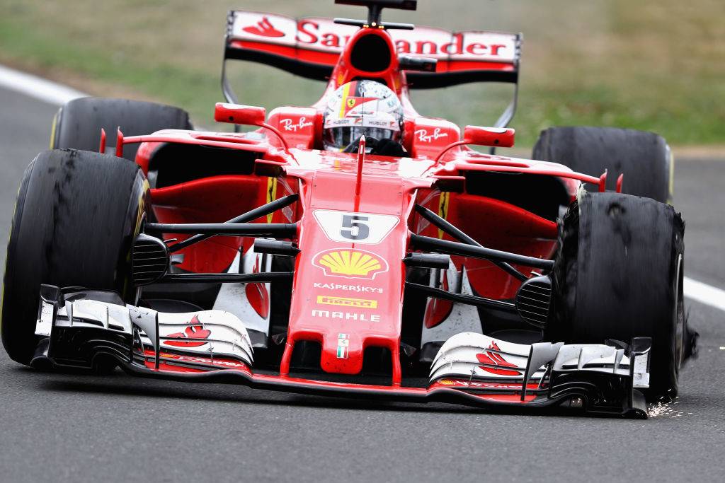 Sebastian Vettel heads for the pits after suffering a puncture.