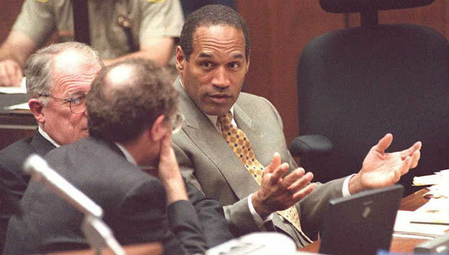 O.J. Simpson (R) talks with two of his attorneys during his trial in 1995.