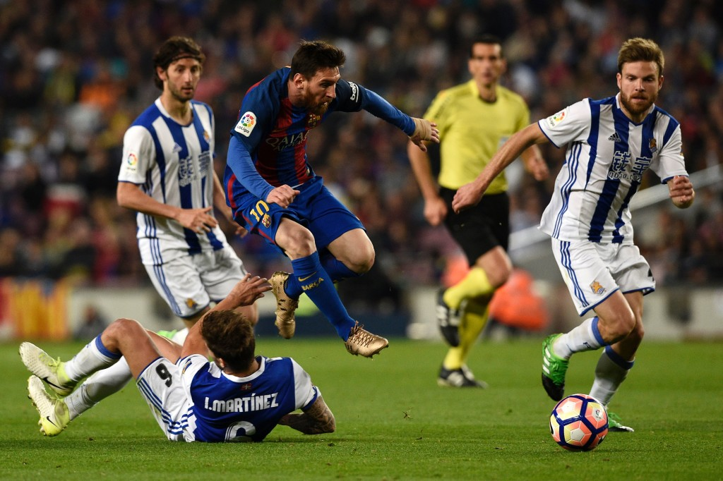 Barcelona's Argentinian forward Lionel Messi (top C) jumps over Real Sociedad's defender Inigo Martinez Berridi (bottom) beside Real Sociedad's midfielder Asier Illarramendi (R) during the Spanish league football match FC Barcelona vs Real Sociedad at the Camp Nou stadium in Barcelona on April 15, 2017. / AFP PHOTO / LLUIS GENE (Photo credit should read LLUIS GENE/AFP/Getty Images)