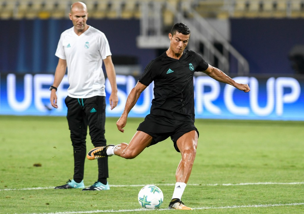 Real Madrid's French head coach Zinedine Zidane (L) looks on as Real Madrid's forward Cristiano Ronaldo shoots the ball during a training session before the UEFA Super Cup 2017 football match between Real Madrid and Manchester United at the National Arena Filip II on August 7, 2017 in Skopje. / AFP PHOTO / NIKOLAY DOYCHINOV (Photo credit should read NIKOLAY DOYCHINOV/AFP/Getty Images)