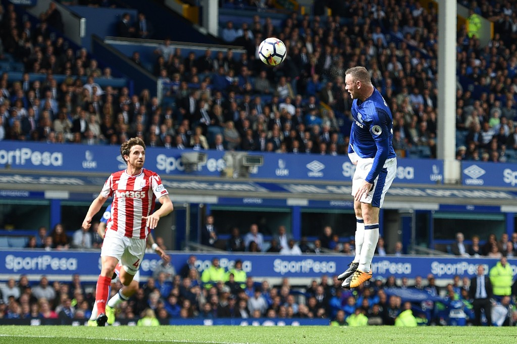 Everton's English striker Wayne Rooney (R) watches the ball after heading to score the openingh goal during the English Premier League football match between Everton and Stoke City at Goodison Park in Liverpool, north west England on August 12, 2017. / AFP PHOTO / Oli SCARFF / RESTRICTED TO EDITORIAL USE. No use with unauthorized audio, video, data, fixture lists, club/league logos or 'live' services. Online in-match use limited to 75 images, no video emulation. No use in betting, games or single club/league/player publications. / (Photo credit should read OLI SCARFF/AFP/Getty Images)
