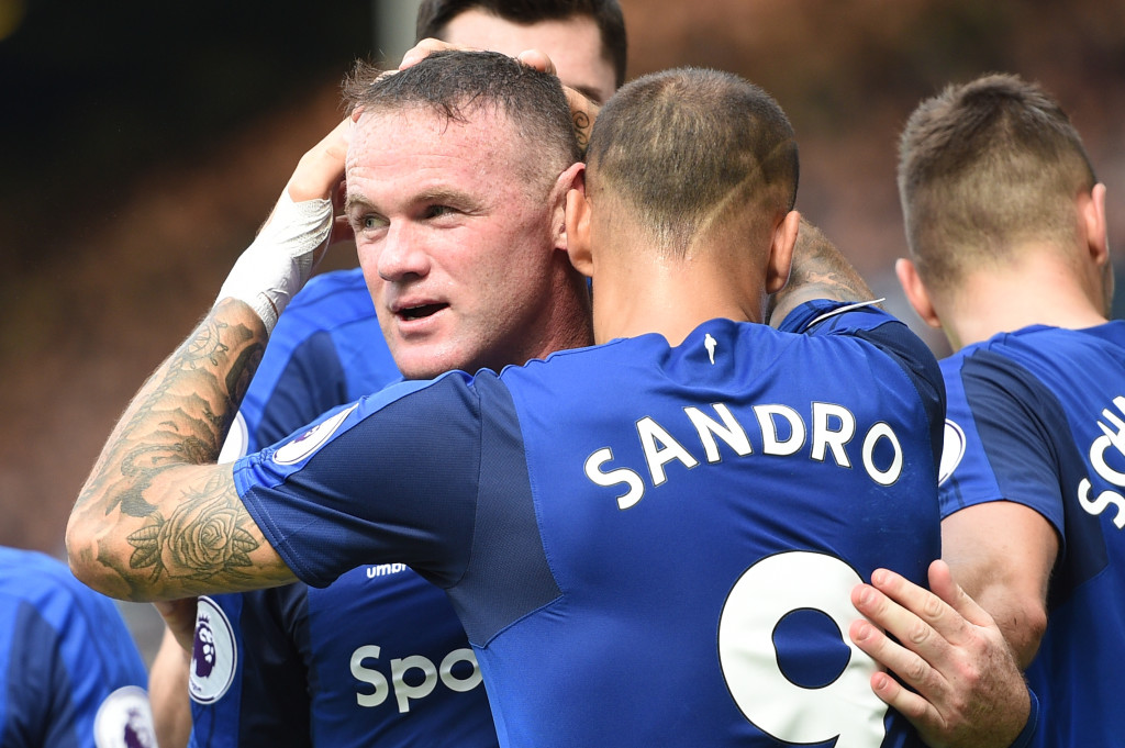 Everton's English striker Wayne Rooney celebrates scoring the opening goal with Everton's Spanish striker Sandro Ramirez during the English Premier League football match between Everton and Stoke City at Goodison Park in Liverpool, north west England on August 12, 2017. / AFP PHOTO / Oli SCARFF / RESTRICTED TO EDITORIAL USE. No use with unauthorized audio, video, data, fixture lists, club/league logos or 'live' services. Online in-match use limited to 75 images, no video emulation. No use in betting, games or single club/league/player publications. / (Photo credit should read OLI SCARFF/AFP/Getty Images)