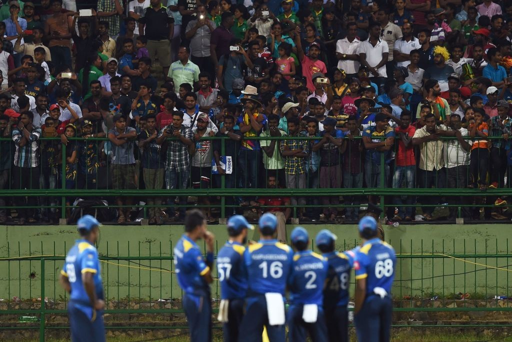 The Sri Lankan players wait for play to resume after crowd trouble in Pallekele on Sunday.