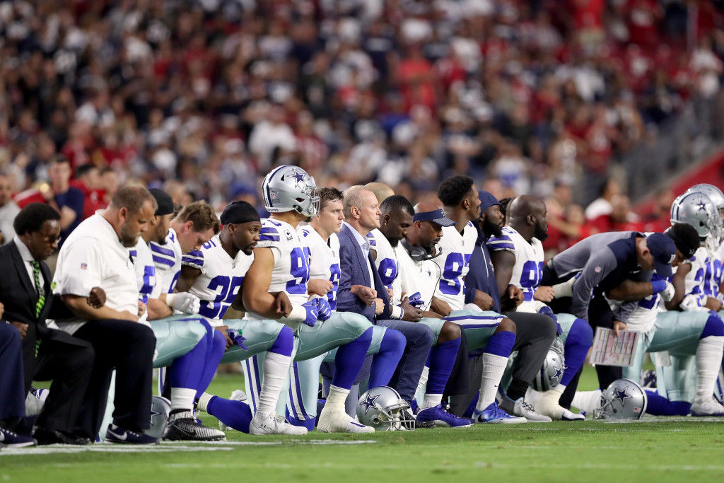 Members of the Dallas Cowboys linked arms and knelt before the anthem on Sunday.