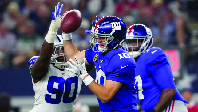 In a rush: Eli Manning faces pressure from the Dallas pass rush. Picture: Getty Images.