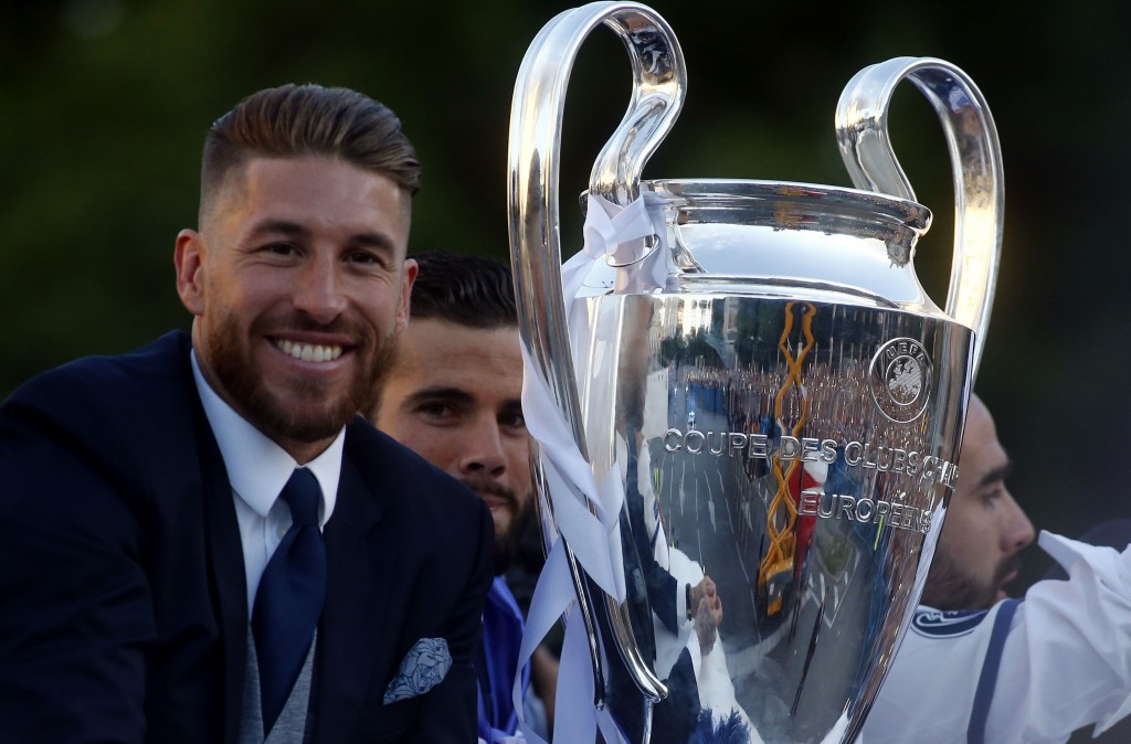 Real Madrid's defender Sergio Ramos (L) smiles beside the trophy celebrating the team's win from an onpen decker bus on Plaza Cibeles in Madrid on June 4, 2017 after the UEFA Champions League football match final Juventus vs Real Madrid CF held at the National Stadium of Wales in Cardiff on June 3, 2017. / AFP PHOTO / OSCAR DEL POZO (Photo credit should read OSCAR DEL POZO/AFP/Getty Images)