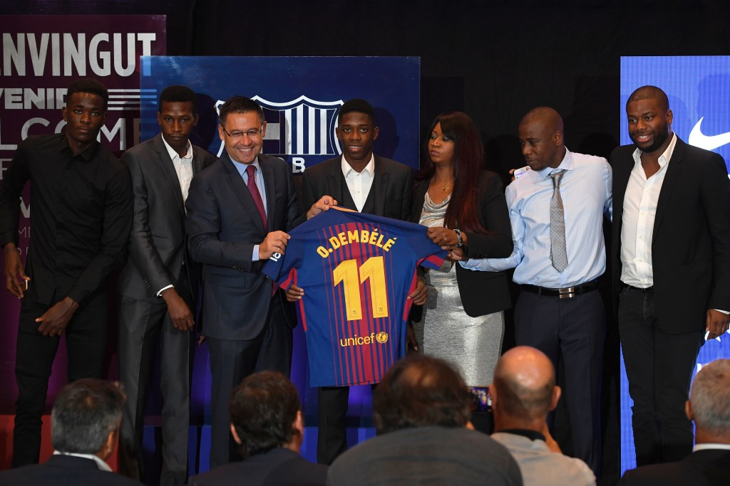 Barcelona's new player Ousmane Dembele (C) poses with his new jersey next to Barcelona's president Josep Maria Bartomeu (3rdL) and Dembele's relatives at the Camp Nou stadium in Barcelona, during his official presentation at the Catalan football club, on August 28, 2017. French starlet Ousmane Dembele agreed a five-year deal with Barcelona worth 105 million euros ($125 million) plus add-ons. Dembele, 20, moves from Borussia Dortmund, where he has been suspended since he boycotted training on August 10 in protest after the German club rejected Barca's first bid. / AFP PHOTO / LLUIS GENE (Photo credit should read LLUIS GENE/AFP/Getty Images)