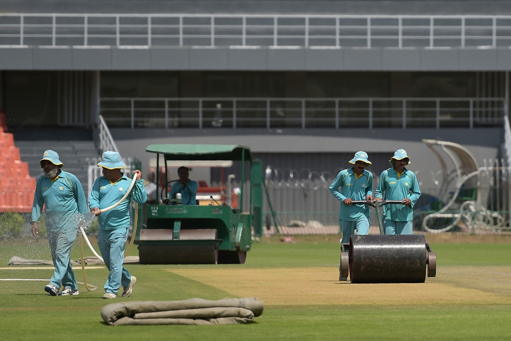 This picture taken on September 7, 2017 shows ground staff preparing the cricket pitch of the Gaddafi Stadium in Lahore.  Groundsmen are rolling down the pitches, welders are repairing barbed wire, and workers are splashing on a new coat of paint at Pakistan's centrepiece Gaddafi Stadium, which has witnessed both history and controversy -- and is now preparing to retake the world stage. / AFP PHOTO / Aamir QURESHI / TO GO WITH Cricket-PAK-Pakistan-Gaddafi, FOCUS by Khurram SHAHZAD        (Photo credit should read AAMIR QURESHI/AFP/Getty Images)