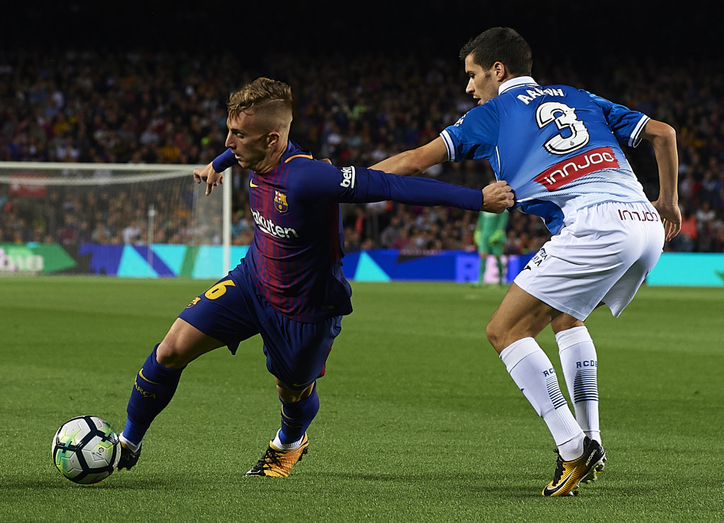 Gerard Deulofeu (L) of Barcelona competes for the ball with Aaron Martin
