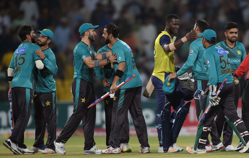 World XI cricketer Darren Sammy (4R) congratulates Pakistani cricketers after winning the third and final Twenty20 International match against World XI at the Gaddafi Cricket Stadium in Lahore on September 15, 2017.  / AFP PHOTO / AAMIR QURESHI        (Photo credit should read AAMIR QURESHI/AFP/Getty Images)