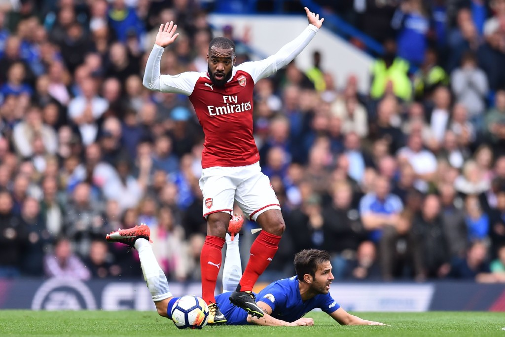 Lacazette competes for the ball with Cesc Fabregas