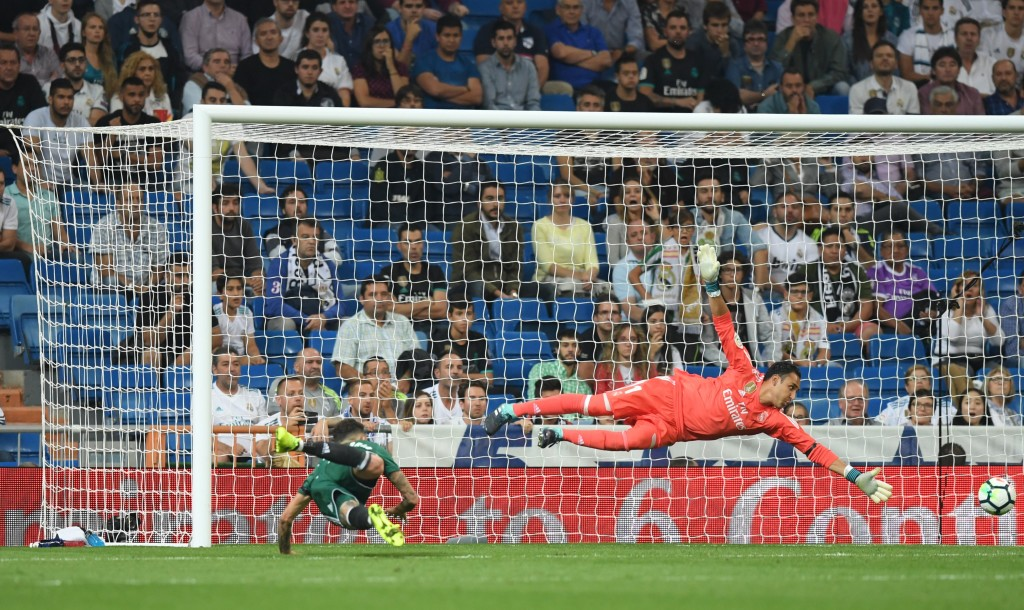 Real Betis' forward from Paraguay Arnaldo Sanabria (L) heads the ball to score a goal as Real Madrid's goalkeeper from Costa Rica Keylor Navas dives for the ball during the Spanish league football match Real Madrid CF against Real Betis at the Santiago Bernabeu stadium in Madrid on September 20, 2017. / AFP PHOTO / GABRIEL BOUYS (Photo credit should read GABRIEL BOUYS/AFP/Getty Images)