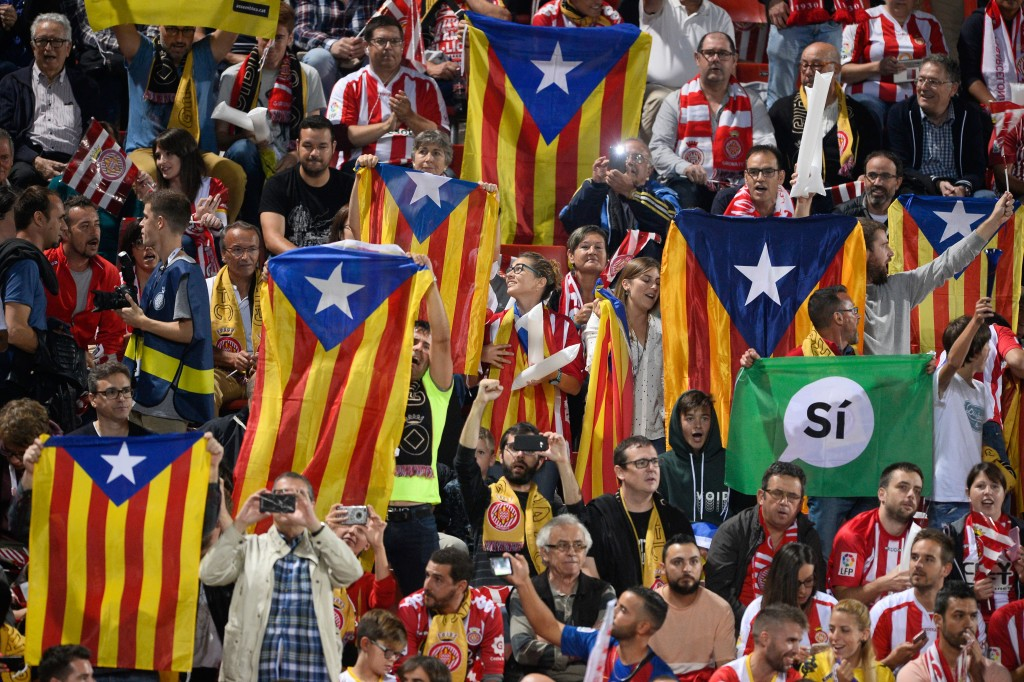 """Catalan football fans hold Esteladas and flag reading """"Yes"""""""
