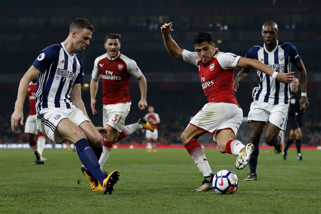 Arsenal's Chilean striker Alexis Sanchez (2R) attempts a Rabona cross but miss-times the pass during the English Premier League football match between Arsenal and West Bromwich Albion at the Emirates Stadium in London on September 25, 2017. / AFP PHOTO / Ian KINGTON / RESTRICTED TO EDITORIAL USE. No use with unauthorized audio, video, data, fixture lists, club/league logos or 'live' services. Online in-match use limited to 75 images, no video emulation. No use in betting, games or single club/league/player publications. / (Photo credit should read IAN KINGTON/AFP/Getty Images)