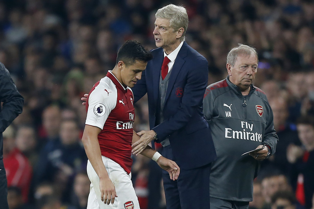 Arsenal's Chilean striker Alexis Sanchez passes Arsenal's French manager Arsene Wenger as he substituted off of the pitch during the English Premier League football match between Arsenal and West Bromwich Albion at the Emirates Stadium in London on September 25, 2017. / AFP PHOTO / Ian KINGTON / RESTRICTED TO EDITORIAL USE. No use with unauthorized audio, video, data, fixture lists, club/league logos or 'live' services. Online in-match use limited to 75 images, no video emulation. No use in betting, games or single club/league/player publications. / (Photo credit should read IAN KINGTON/AFP/Getty Images)