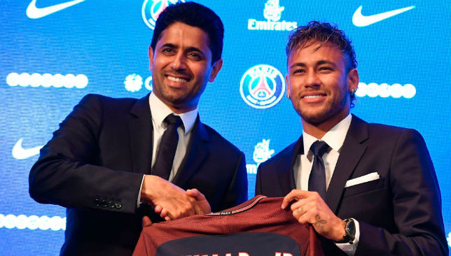 Neymar (R) poses with his jersey next to Paris Saint Germain's (PSG) Qatari president Nasser Al-Khelaifi