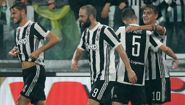 Paulo Dybala celebrates with his team-mates after scoring a goal.