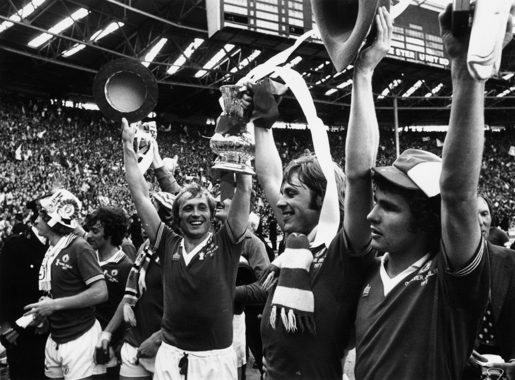 21st May 1977: Brian Greenhoff (centre) lifting the FA Cup with his brother Jimmy who scored Manchester United's second and winning goal in the final against Liverpool at Wembley. (Photo by Roger Jackson/Central Press/Getty Images)