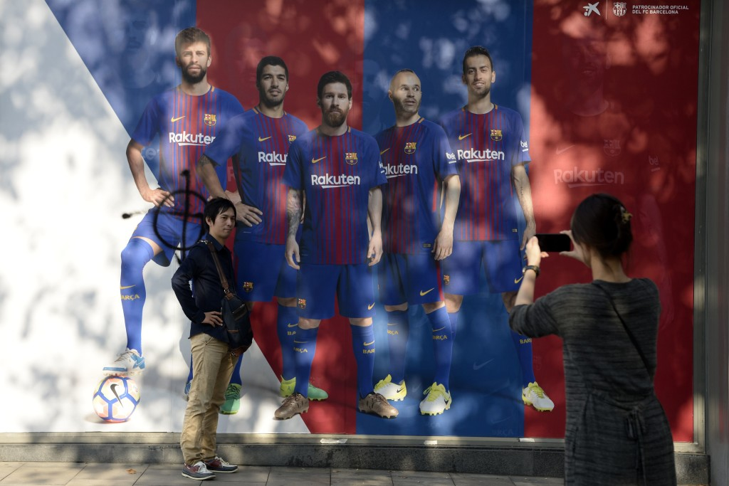 "A fan poses in front of a poster of Barcelona FC where the picture of defender Gerard Pique has been vandalised outside the club's Camp Nou stadium which was closed as part of a general strike in Barcelona called by Catalan unions on October 3, 2017. Several hundred thousand Catalans rallied in fury at police violence against voters during a banned independence referendum, as Madrid accused regional authorities of ""inciting rebellion"". Barcelona football club refused to train as part of an accompanying strike, which officials said slowed down public transport and freight shipments in the port of Barcelona. Pique is an outspoken defender of the wealthy northeastern Spanish region's right to self-determination. / AFP PHOTO / Josep LAGO (Photo credit should read JOSEP LAGO/AFP/Getty Images)"