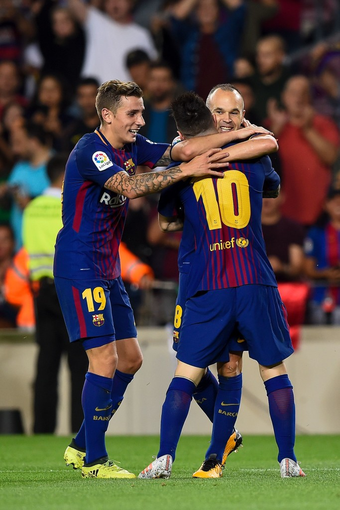 Barcelona's midfielder Andres Iniesta (R) is congratulated by his teammates Barcelona's French defender Lucas Digne (L) and Barcelona's Argentinian forward Lionel Messi after scoring a goal during the Spanish league football match FC Barcelona vs Malaga CF at the Camp Nou stadium in Barcelona on October 21, 2017. / AFP PHOTO / Josep LAGO (Photo credit should read JOSEP LAGO/AFP/Getty Images)