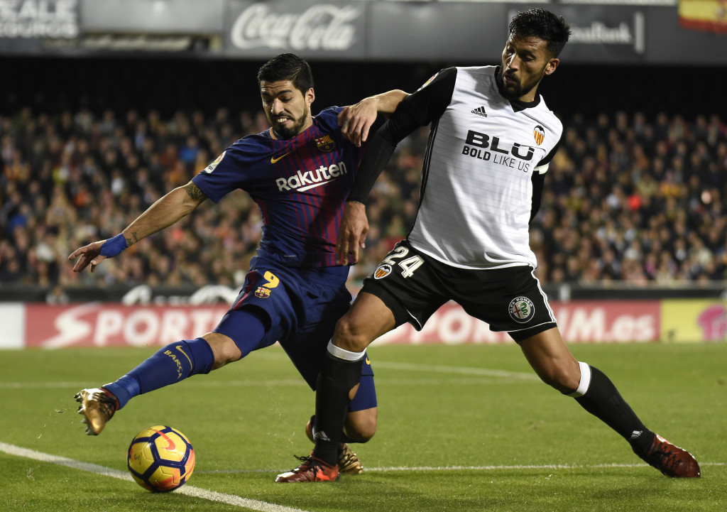 Luis Suarez (L) battles for the ball with Valencia's Ezequiel Garay