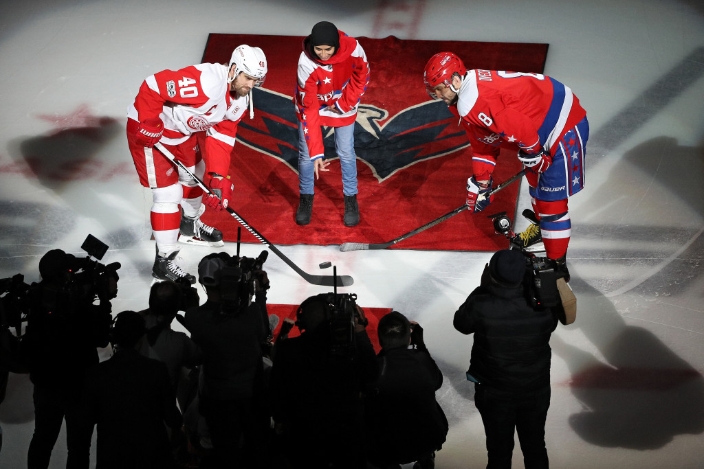 Fatima Al Ali takes part in a ceremonial puck drop between Henrik Zetterberg #40 of the Detroit Red Wings and Alex Ovechkin #8 of the Washington Capitals.