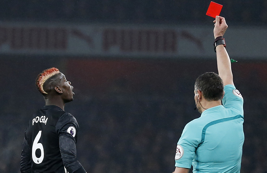 Referee Andre Marriner shows a red card to Paul Pogba