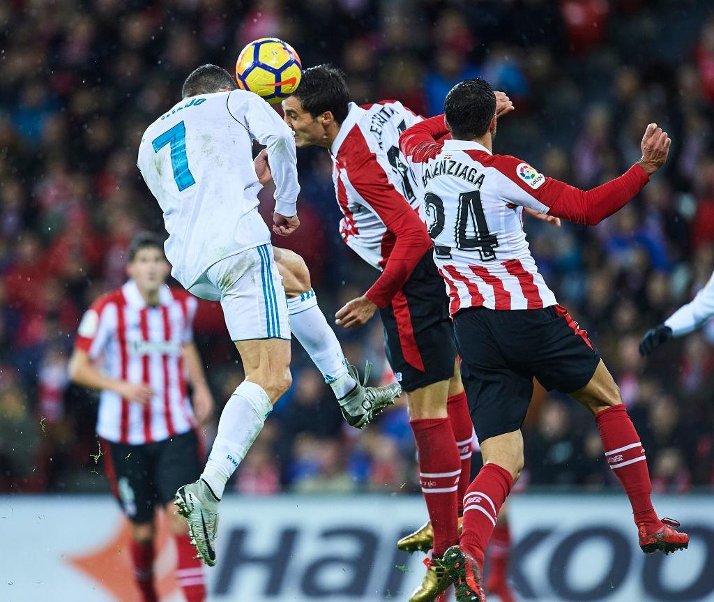 Cristiano Ronaldo competes with Xavier Etxeita (R)
