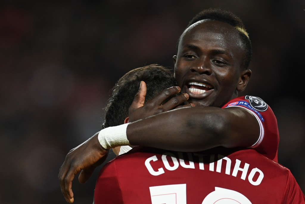 Liverpool's Brazilian midfielder Philippe Coutinho (L) celebrates scoring their fifth goal with Liverpool's Senegalese midfielder Sadio Mane (R) during the UEFA Champions League Group E football match between Liverpool and Spartak Moscow at Anfield in Liverpool, north-west England on December 6, 2017. / AFP PHOTO / Paul ELLIS