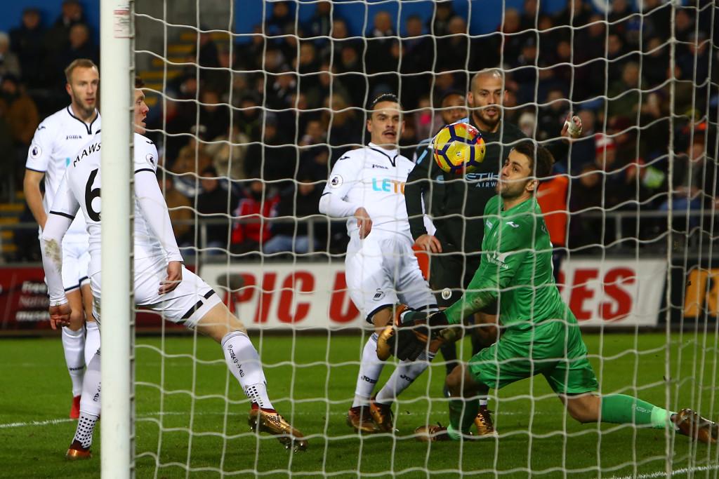 David Silva (C) lifts the ball over Lukasz Fabianski for his second
