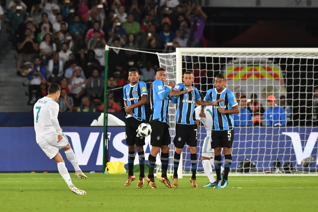Real Madrid's Portuguese forward Ronaldo (L) curls the ball over the Gremio wall to score from a free-kick during their FIFA Club World Cup 2017 final football match at Zayed Sports City Stadium in the Emirati capital Abu Dhabi on December 16, 2017. / AFP PHOTO / Giuseppe CACACE        (Photo credit should read GIUSEPPE CACACE/AFP/Getty Images)
