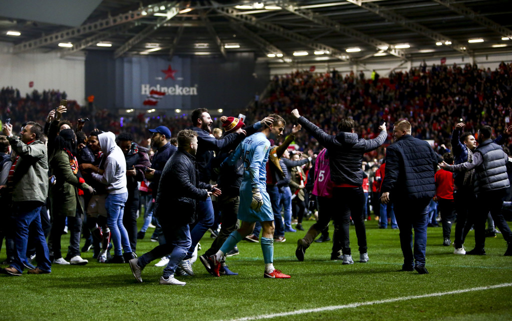 Bristol City fans celebrate their victory as they invade the pitch after the English League Cup quarter-final football match between Bristol City and Manchester United at Ashton Gate Stadium in Bristol, southwest England on December 20, 2017. / AFP PHOTO / Geoff CADDICK / RESTRICTED TO EDITORIAL USE. No use with unauthorized audio, video, data, fixture lists, club/league logos or 'live' services. Online in-match use limited to 75 images, no video emulation. No use in betting, games or single club/league/player publications. / (Photo credit should read GEOFF CADDICK/AFP/Getty Images)
