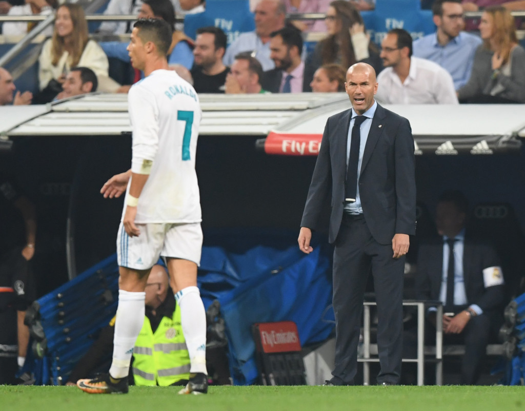 Real Madrid's coach from France Zinedine Zidane (R) gives instructions from the sideline as Real Madrid's forward from Portugal Cristiano Ronaldo walks past during the Spanish league football match Real Madrid CF against Real Betis at the Santiago Bernabeu stadium in Madrid on September 20, 2017. / AFP PHOTO / GABRIEL BOUYS (Photo credit should read GABRIEL BOUYS/AFP/Getty Images)