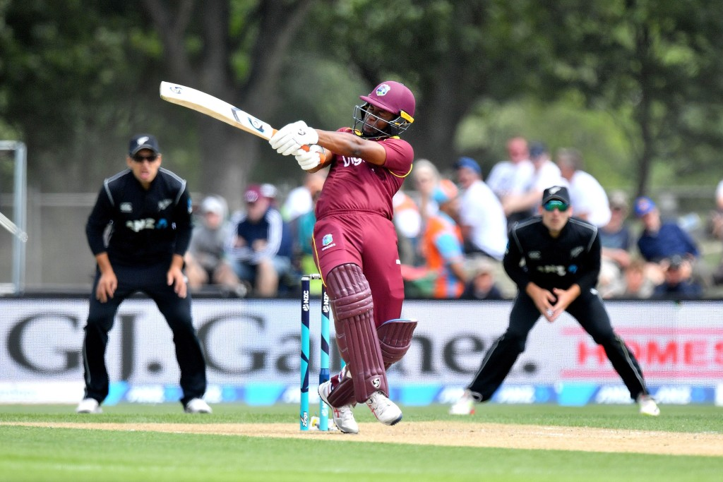 West Indies player Evin Lewis (C) bats as New Zealand's Ross Taylor (L) and Tom Latham (R) look on, during the second one-day international (ODI) cricket match between New Zealand and the West Indies at Hagley Oval in Christchurch on December 23, 2017. / AFP PHOTO / Marty MELVILLE (Photo credit should read MARTY MELVILLE/AFP/Getty Images)