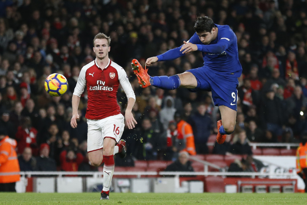Chelsea's Spanish striker Alvaro Morata (R) has a shot on goal by Arsenal's English defender Rob Holding during the English Premier League football match between Arsenal and Chelsea at the Emirates Stadium in London on January 3, 2018. / AFP PHOTO / Ian KINGTON / RESTRICTED TO EDITORIAL USE. No use with unauthorized audio, video, data, fixture lists, club/league logos or 'live' services. Online in-match use limited to 75 images, no video emulation. No use in betting, games or single club/league/player publications. / (Photo credit should read IAN KINGTON/AFP/Getty Images)