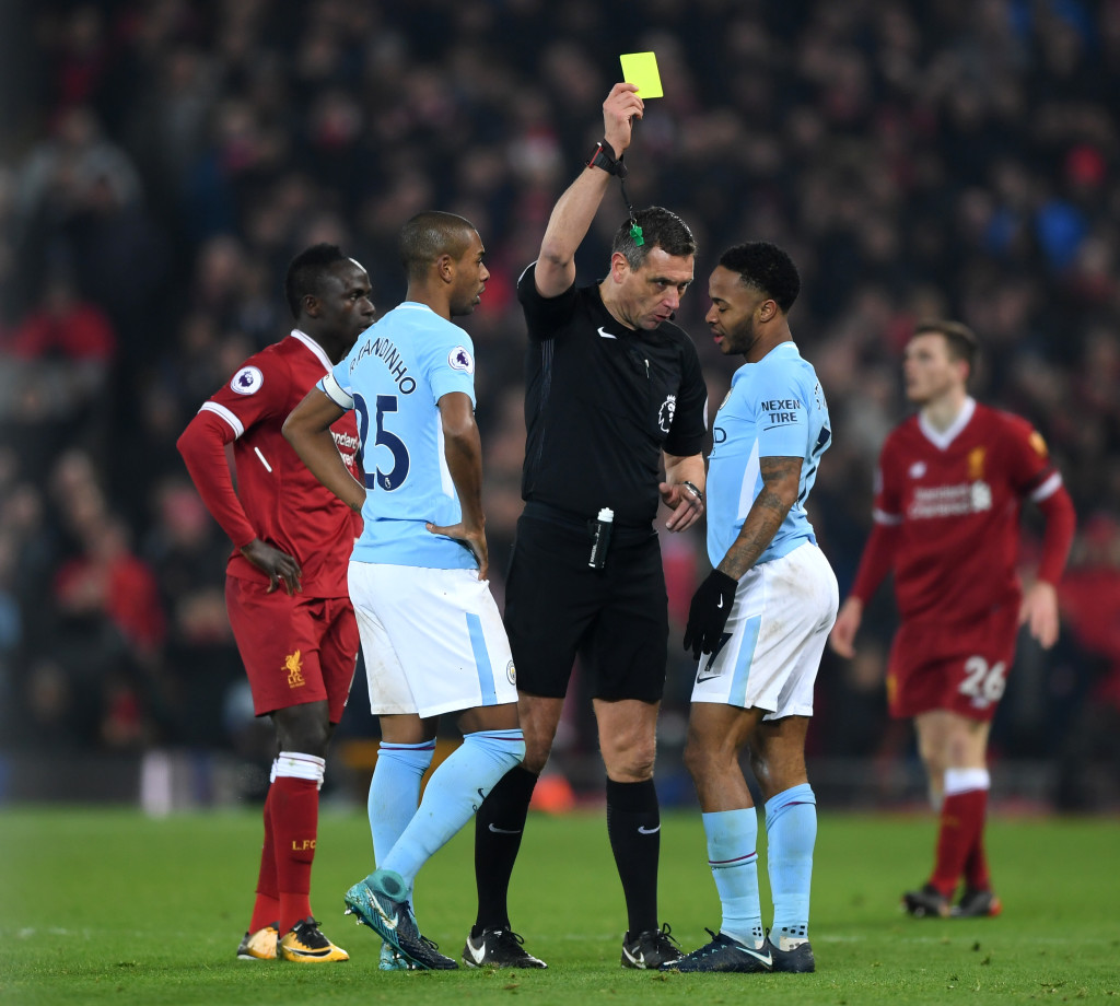 LIVERPOOL, ENGLAND - JANUARY 14: Raheem Sterling of Manchester City is shown a yellow card by referee Andre Marriner during the Premier League match between Liverpool and Manchester City at Anfield on January 14, 2018 in Liverpool, England. (Photo by Shaun Botterill/Getty Images)