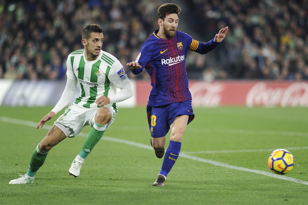 Barcelona's Argentinian forward Lionel Messi (R) challenges Real Betis' Moroccan defender Zou (L) during the Spanish league football match between Real Betis and FC Barcelona at the Benito Villamarin stadium in Sevilla on January 21, 2018. / AFP PHOTO / CRISTINA QUICLER (Photo credit should read CRISTINA QUICLER/AFP/Getty Images)