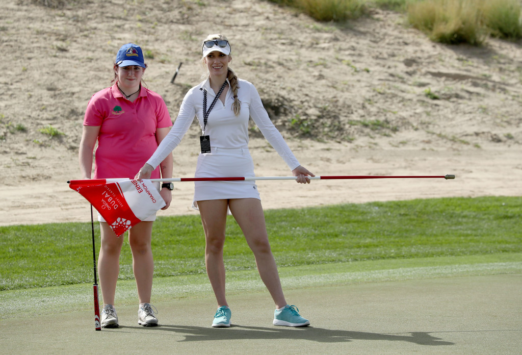 DUBAI, UNITED ARAB EMIRATES - JANUARY 24: Saoirse Lambe of Ireland who won a global competition to play with Rory McIlroy and Niall Horan is assited by Paige Spiranac of the United States during the pro-am as a preview for the Omega Dubai Desert Classic on the Majlis Cours at Emirates Golf Club on January 24, 2018 in Dubai, United Arab Emirates. (Photo by David Cannon/Getty Images)